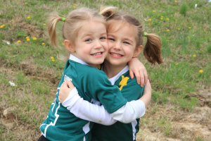 soccer sisters hugging after the game